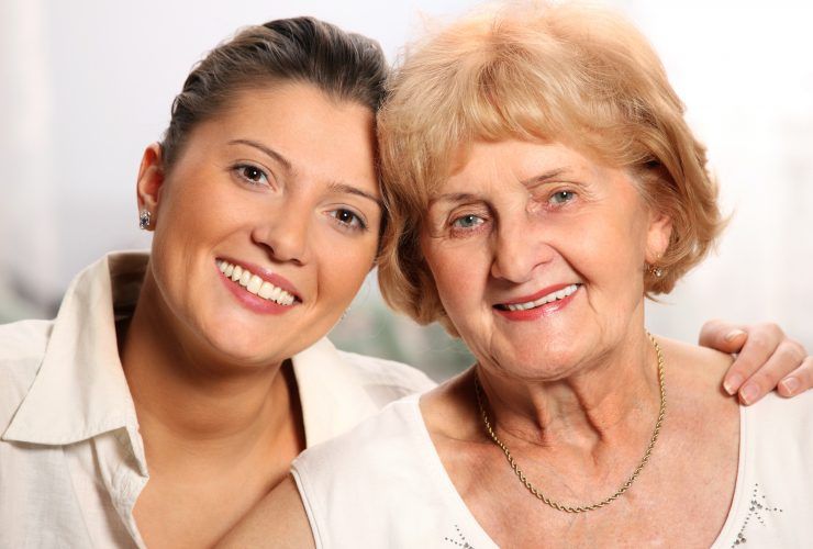 A beautiful portrait of grandma and grandaughter smiling over white background