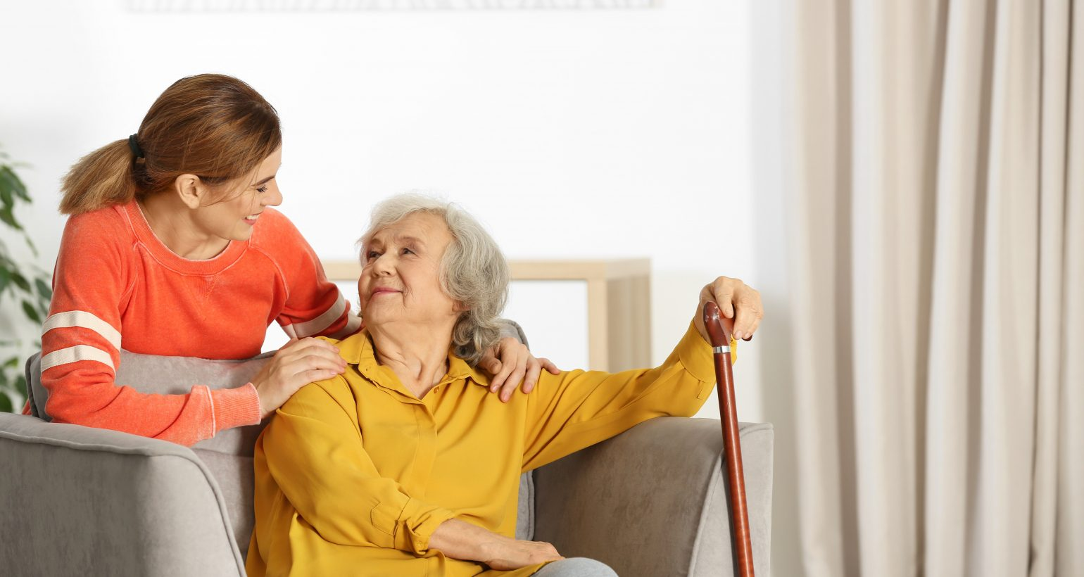 Elderly woman with female caregiver in living room