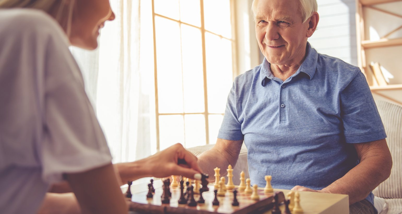 elderly man playing chess with his caregiver